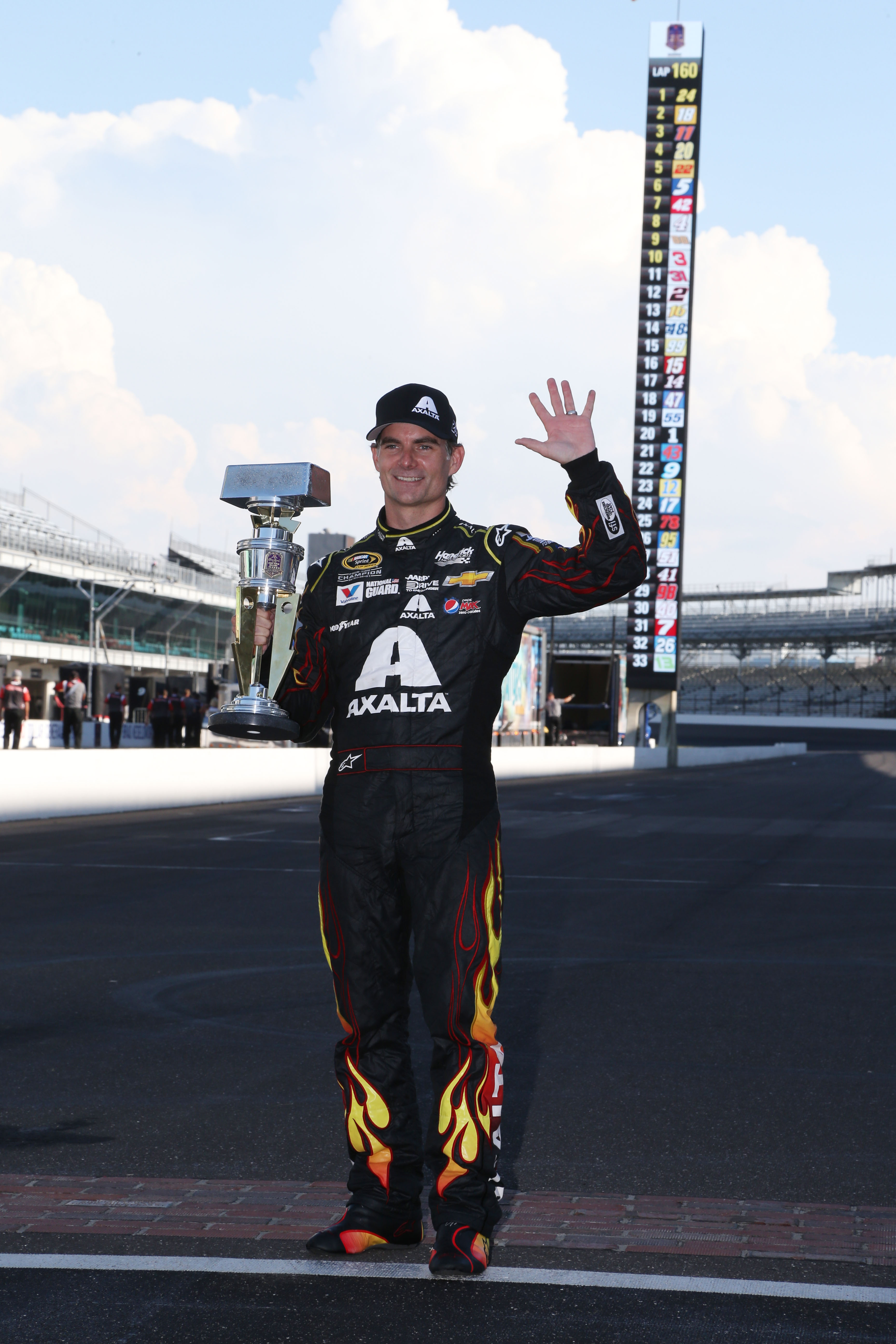 Jul 27, 2014; Speedway, IN, USA; NASCAR Sprint Cup driver Jeff Gordon who became a five time Brickyard 400 winner poses with the trophy and holds up five fingers after winning the Crown Royal Brickyard 400 at Indianapolis Motor Speedway. Mandatory Credit: Brian Spurlock-USA TODAY Sports